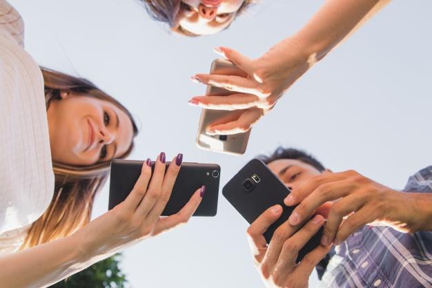from-below-view-of-teens-with-smartphones_23-2147659321